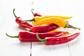 Red yellow chili peppers wooden background — Stock Photo