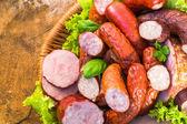 Vari carne salsiccia cesto tavolo in legno sfondo — Foto Stock