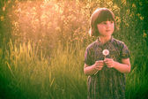 Smiling Pretty little girl dandelions field rape — Stock Photo