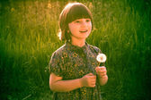 Smiling Pretty little girl dandelions field rape — Zdjęcie stockowe
