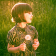 Smiling Pretty little girl dandelions field rape — Stock Photo #48469209