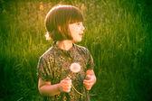Smiling Pretty little girl dandelions field rape — Stock Photo
