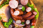 Various meat sausage basket wooden table background — Stock Photo