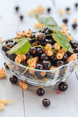Fruits white black currants saucer wooden table — Stock Photo