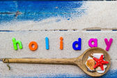 Word holiday laid sand blue board — Photo