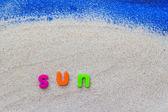 Word sun laid sand blue board — Photo