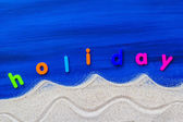 Word holiday laid sand blue board — Stockfoto