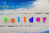 Word holiday laid sand blue board — Stock Photo