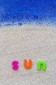 Word sun laid sand blue board — Stock Photo