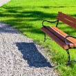 Bench in the park on a background of grass — Stok fotoğraf