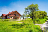 New house on spring field — Stock Photo