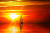Sailboat on the ocean at sunset — Stock Photo