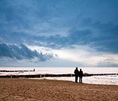 Couple on the beach at sunset — Stock Photo