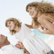 Portrait of young family having fun on the beach — Stock Photo #12586452