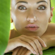 Portrait of young beautiful woman on green leafs back — Stock Photo #12622548