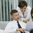 Portrait of young business discussing project in office environment - Stock Photo