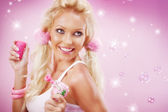 Portrait of young nice woman with soap bubbles on pink back — Stock Photo