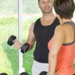 Portrait of young nice couple getting busy in gym - ストック写真