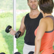 Portrait of young nice couple getting busy in gym - Photo