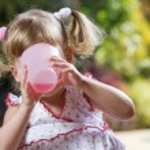 Portrait of little girl having drink in summer environment — Stock Photo