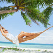 View of nice young lady swinging in hummock on tropical beach — ストック写真