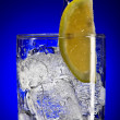 Close up view of iced tonic glass with lemon on blue back — Stock Photo