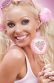 Portrait of young nice woman with lollypop on pink back — Stock Photo