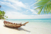 View of nice tropical beach with old boat — Stock Photo