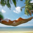 View of nice woman lounging in hammock in tropical environment — Stock Photo #25908847