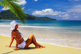 View of nice woman lounging on tropical beach in white panama and bikini — Stock Photo