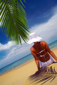 View of nice woman lounging on tropical beach in white panama and bikini — Stock fotografie