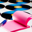 View of compact discs and paper with pen on white sheet - Stock Photo