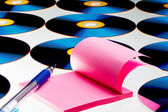 View of compact discs and paper with pen on white sheet — Stock Photo