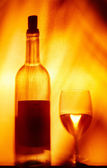 View of wineglasses and bottle silhouette on fire color back — Stock Photo