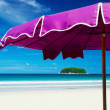 View of nice violet umbrella and small tropic island in the distance — Stock Photo