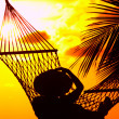 View of a woman lounging in hammock during sunset - Stock Photo