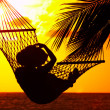View of a woman lounging in hammock during sunset — ストック写真