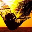 View of a woman lounging in hammock during sunset — Stock Photo