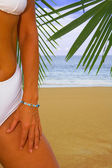 View of a fragment of womans body in white bikini on tropical beach — Stock Photo