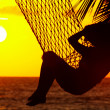 View of a woman lounging in hammock during sunset — Stok fotoğraf