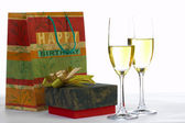 View of packed present and two glasses of white wine — Stock Photo