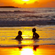 Stock Photo: View of two kids silhouettes on beach during sunset