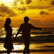 Stock Photo: View of young couple walking along shore during sunset