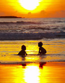 View of two kids silhouettes on the beach during sunset — Stock Photo