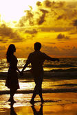 View of young couple walking along the shore during sunset — Stockfoto