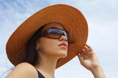 View of nice woman in black swimming wear holding her straw hat — Stock Photo