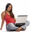 View of young cute emotional brunette sitting behind her laptop — Stock Photo #25957861