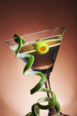 View of martini glass with vermouth and curl of lime rind — Stock Photo