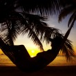 Stock Photo: View of womlounging in hammock during sunset