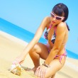 Portrait of a young gorgeous female on beach picking up sea shell — Stock Photo